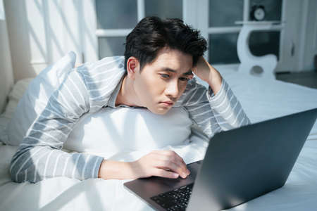 A man lie down on the white bed while he work from home as the company's policy due to disease outbreaks, he getting bored while his project get a problem.