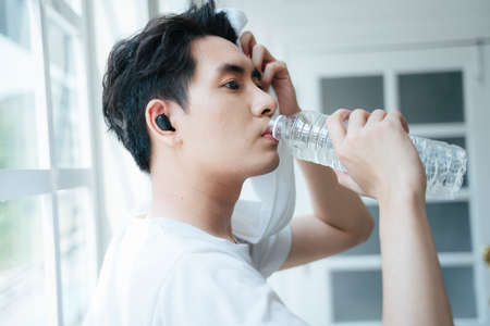 A man stop workout and drinking the water while wipe the sweat.