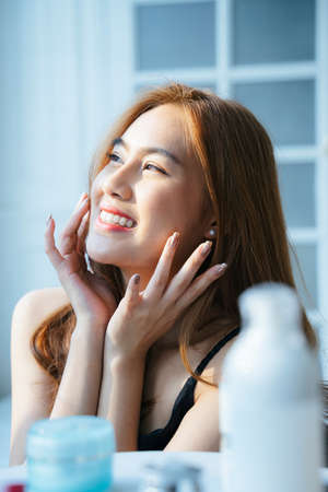 Wavy blond hair girl is happy while apply facial cream on her face to ger younger.