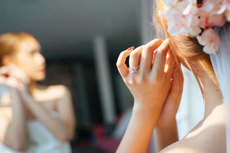 Pony tail blond hair woman get dress up in the morning of her wedding day, cropped image of bride's hands while her put on the earring. Foto de archivo