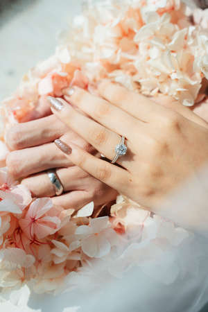Cropped image of man and woman's hands on the beautiful flowers wih ring on the wedding rings fingers.