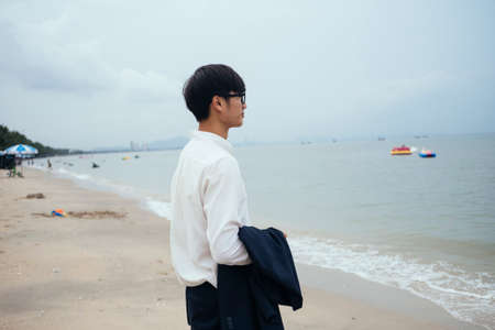 Black hair guy in white shirt standing on the beach and look at the sea.
