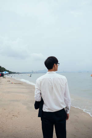 Black hair guy in white shirt walking out of the camera on the beach and look at the sea.