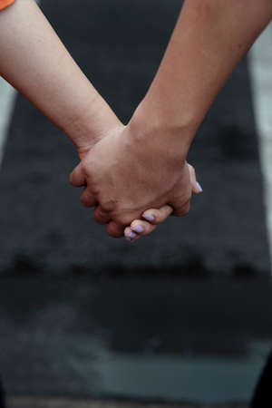 Cropped image of couple's holding hand on the road.