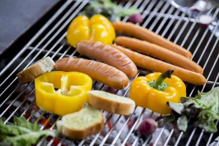 Fresh sausage and hot dogs grilling outdoors on a gas barbecue grill photo