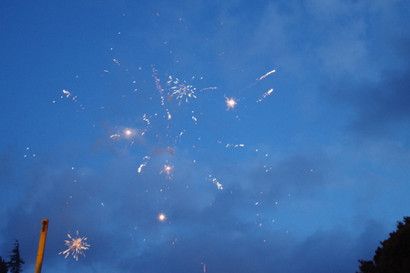 fireworks by day shot by winter in Sardinia, to celebrate the carnival. Colored and sparkling lights in the blue sky.