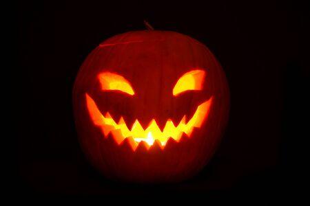 Illuminated Halloween pumkin in darkness