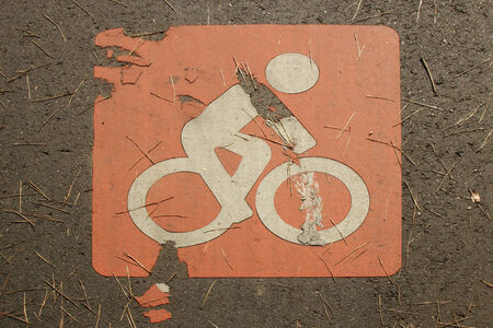 Bicycle sign on a street with grass  photo