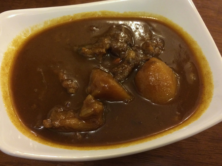 Stewed beef with sweet potato in a white bowl