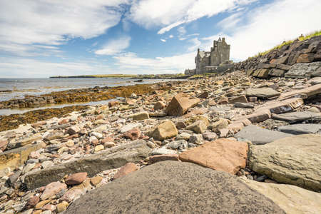 Historic hotel of Ackergill Tower at Sinclair Bay in the Scottish Highlands. Rocky beach with the beautiful and luxuary old british mansion in the background. Cloudy but sunny day at Wick, Scotland.