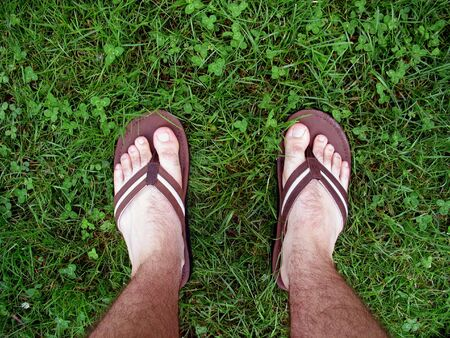 feet with sandals walking through some fresh, green grass photo