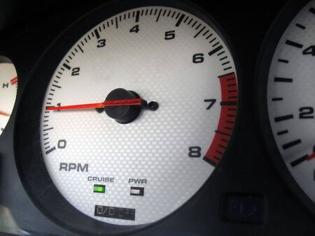 bezel: A custom gauge cluster found in the interior of a sports car.  The dials are a white carbon fiber finish. Stock Photo