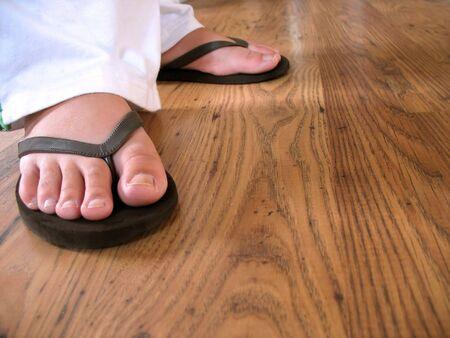 A closeup of a womans feet wearing some black flip flops.