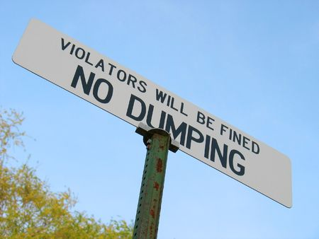 A sign that reads NO DUMPING - VIOLATORS WILL BE FINED.  Great for the going green environmental movement.
