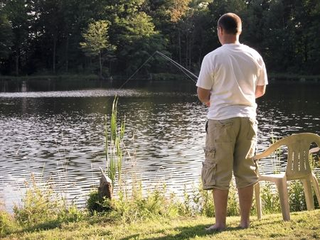 wet t shirt: A lone fishermen fishing in a rural pond.
