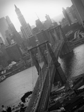 A black and white aerial shot of the famous Brooklyn Bridge and NYC skyline.