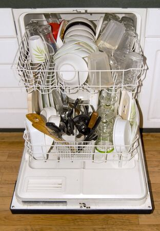 A full dishwasher - ready to go. It is all loaded up with dirty dishes. photo