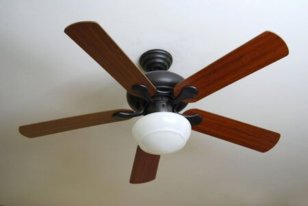 ceiling lamps: A modern ceiling fan, installed on a textured white ceiling. Stock Photo