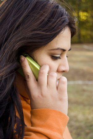 A beautiful young woman of latin descent talking on a cell phone. Stock Photo - 2900279