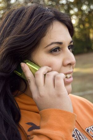 A beautiful young woman of latin descent talking on a cell phone. Stock Photo - 2920349