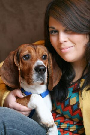 Portrait of a girl in her twenties posing with a young purebred beagle pup. Stock Photo - 2920342