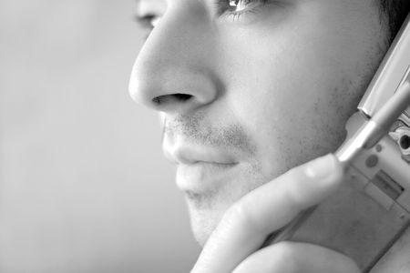 preocupacion: En blanco y negro retrato de un joven en su celly tel�fono. �l est� a la escucha con un aspecto de grave preocupaci�n en su rostro.