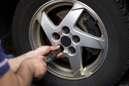 domestic garage: Close-up detail of a mechanic tightening or lossening the lugs of an aluminum rim. Stock Photo