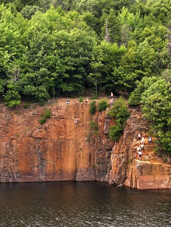 Some crazy kids cliff jumping off the side of a mountain from 60 feet up into the water below.   Stock Photo