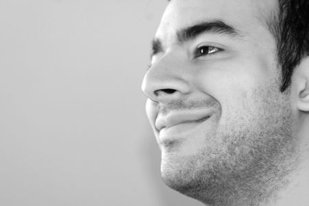 Black and white portrait of a young man smiling - plenty of copy space to the left. photo