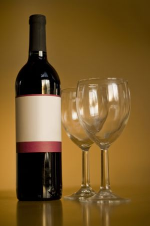 A still life shot of a single wine bottle and a pair of empty glasses.  The label provides copy space for any logo or type desired. photo