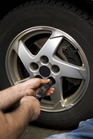 domestic garage: Close-up detail of a mechanic tightening or loosening the lugs of an aluminum rim.
