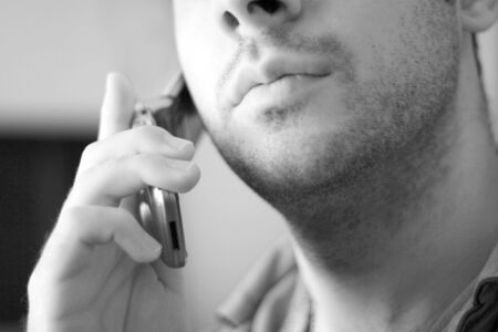 mouth close up: Black and white portrait of an unshaven young man talking on his celly phone.