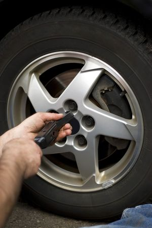 lugs: Close-up detail of a mechanic tightening or lossening the lugs of an aluminum rim. Stock Photo