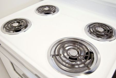 gas stove: A white electric stove with four burners.