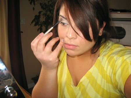 A young Spanish woman applying makeup in front of an illuminated cosmetic mirror. photo