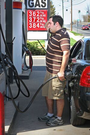 priced: A man pumping high priced gas into his car with a disgusted look on his face. Stock Photo