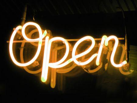 ventanas abiertas: Una naranja ne�n OPEN signo brillante en la ventana de un restaurante.
