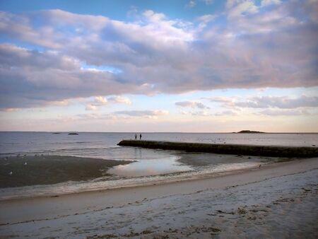 カップルはコネチカット州のビーチで干潮時に石の jeddy に立っています。