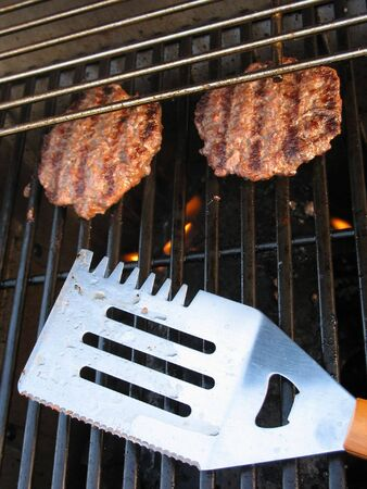 grill: Two hamburgers cooking on the grill. Stock Photo