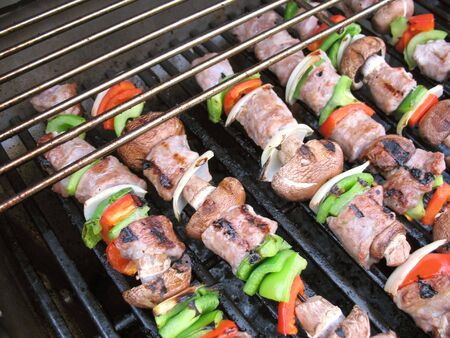 Sausage shish kebabs on skewers, cooking on the grill   photo