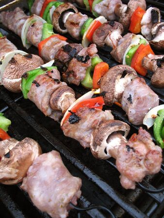 Sausage shish kebabs on skewers, cooking on the grill.  Shallow depth of field. photo