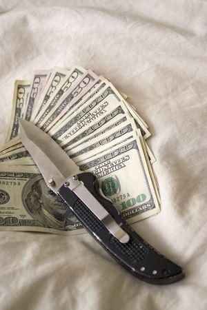 A knife and some fanned out cash laying on a bed. photo