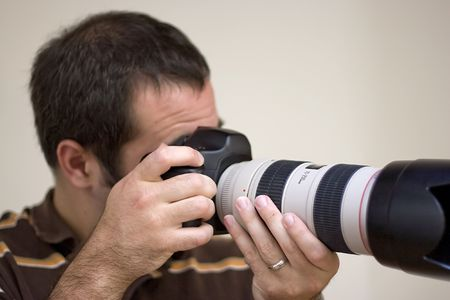 A photographer shooting with a telephoto lens.  Shallow depth of field. photo