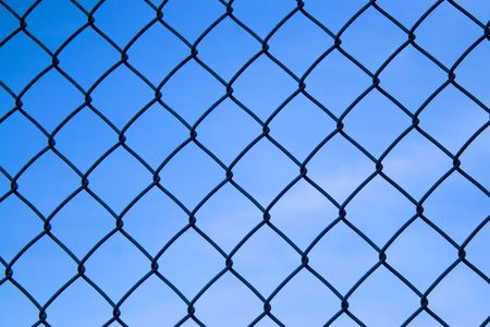 detain: Closeup detail of a chain link fence over a blue sky.