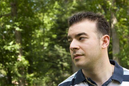 �spiked: Un hombre joven italiano con el pelo de pinchos de pie delante de un fondo arbolado.