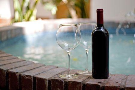 vin chaud: Une bouteille de vin rouge et deux verres vides près de la piscine. Banque d'images