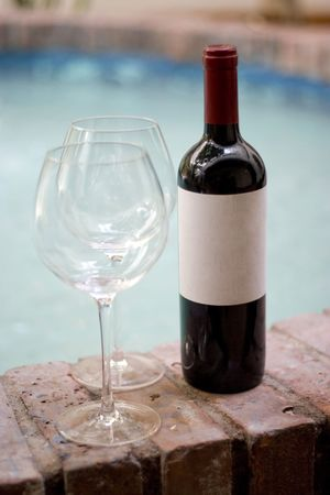 A red wine bottle and two empty glasses by the pool.  Plenty of copy space on the blank wine label. photo