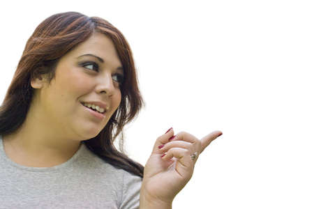 A young hispanic woman pointing to the right.  Plenty of copy space. photo