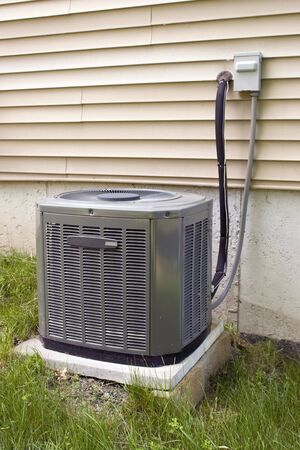 air conditioner: A residential central air conditioning unit sitting outside a home.