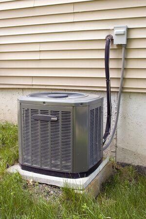 aire acondicionado: Un residencial de aire acondicionado central unidad sesi�n fuera de un hogar.  Foto de archivo